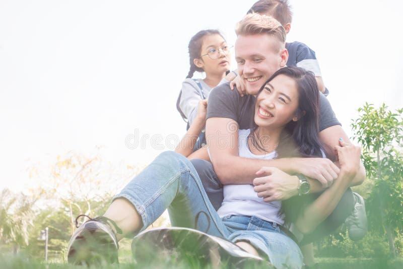 Familie, die im Garten sich entspannt Junge Familie mit den Kindern, die Spaß in der Natur haben stockfoto