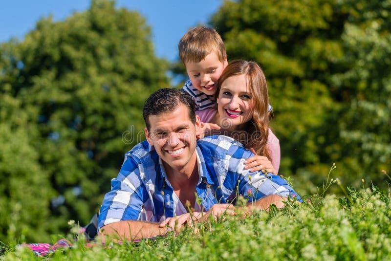 Familie, die im Gras auf einander liegt stockfoto