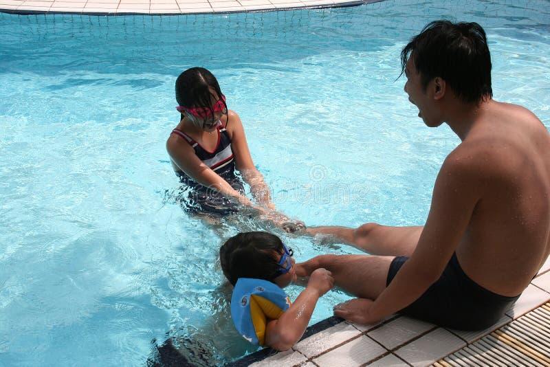 Familie, die im Pool spielt stockfoto