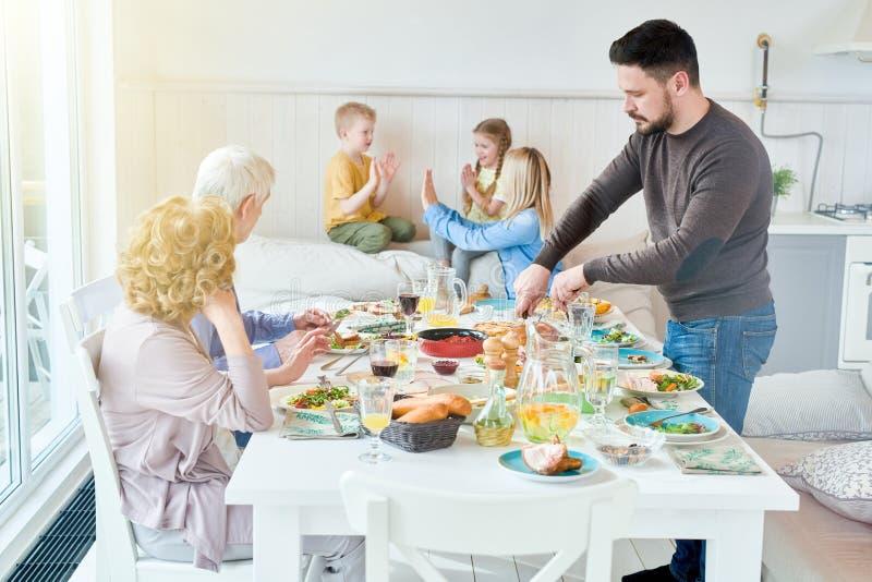 Familie, die im Sonnenlicht Abendessen genießt stockfotografie