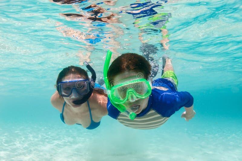 Familie, die im tropischen Wasser schnorchelt lizenzfreie stockbilder