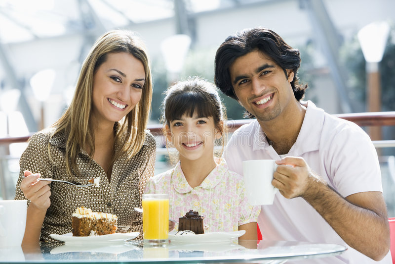 Familie, die Imbiß am Kaffee isst stockfoto