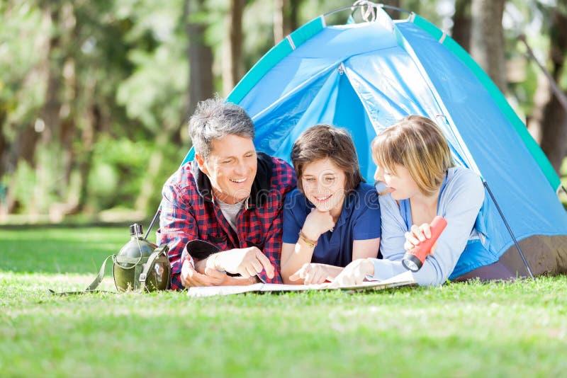 Familie, die Karte beim Lügen im Zelt studiert stockfotos