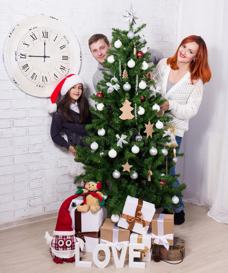 Familie die Kerstboom in woonkamer verfraaien stock afbeelding