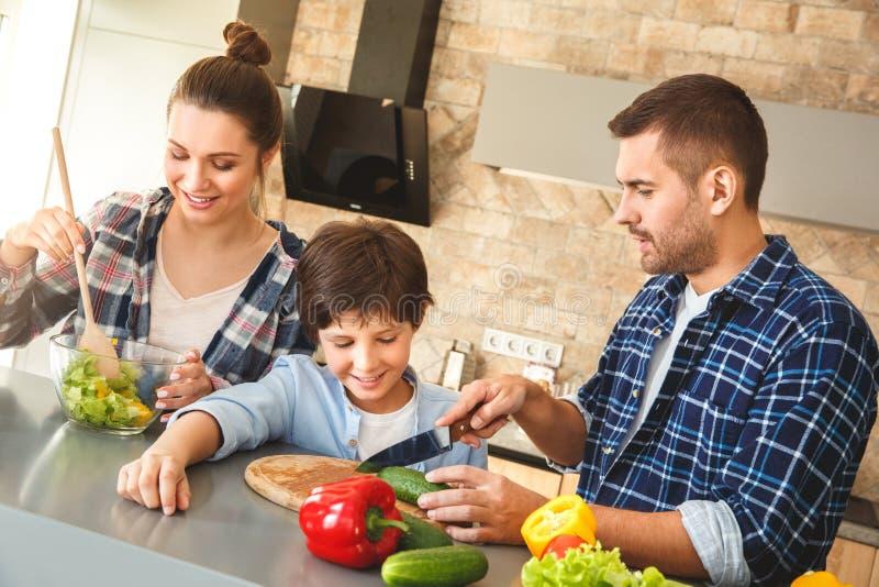 Familie die in keuken zich vader thuis verenigen die zoon scherpe groenten tonen terwijl moeder die gelukkige salade mengen stock foto