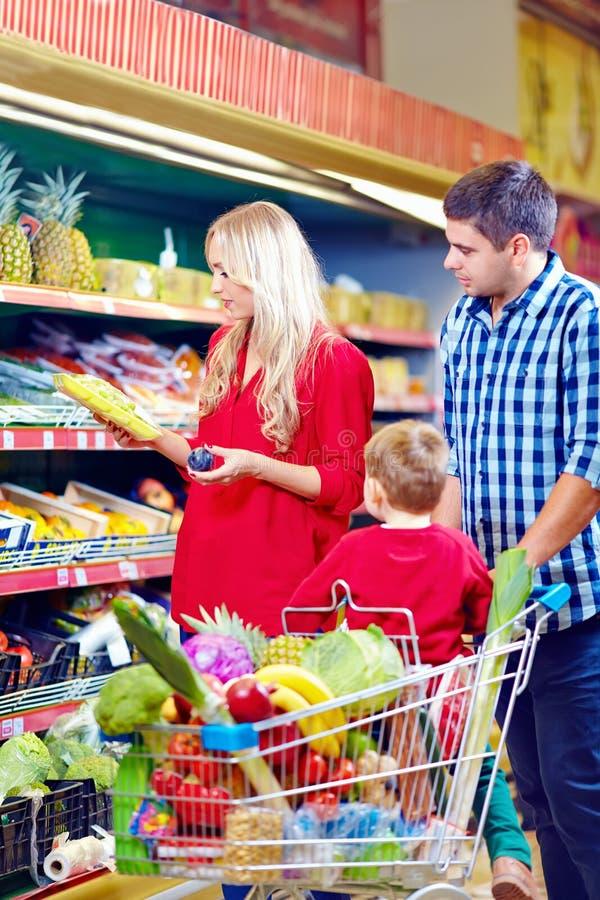 Familie die in kruidenierswinkelmarkt winkelen stock foto's