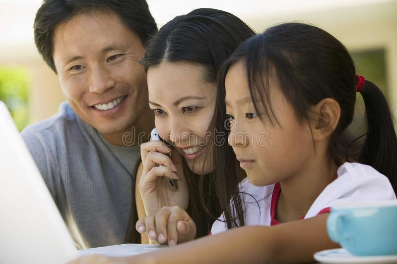 Familie die Laptop in binnenplaats met behulp van royalty-vrije stock afbeelding