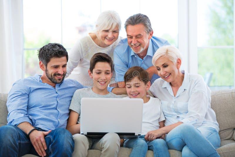 Familie die laptop op een bank met behulp van stock afbeelding