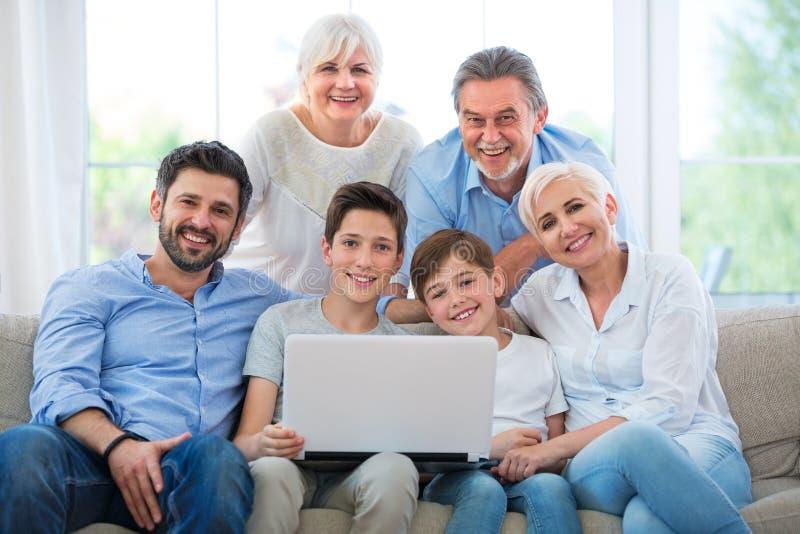 Familie die laptop op een bank met behulp van stock foto's
