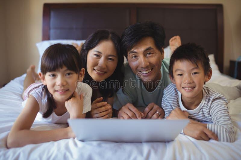 Familie die laptop samen in slaapkamer met behulp van thuis royalty-vrije stock foto