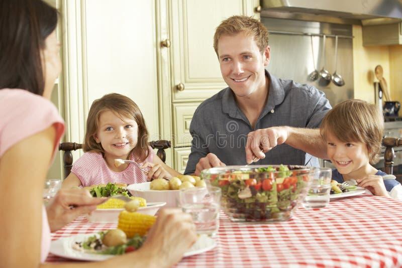 Familie die Maaltijd samen in Keuken eten royalty-vrije stock foto
