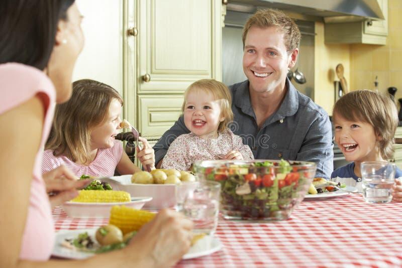 Familie die Maaltijd samen in Keuken eten stock fotografie
