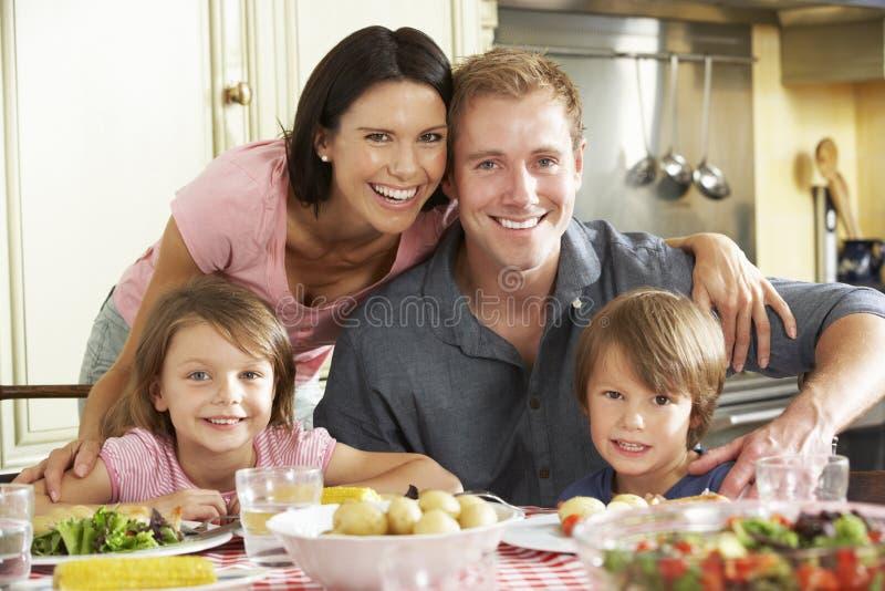 Familie die Maaltijd samen in Keuken eten stock foto