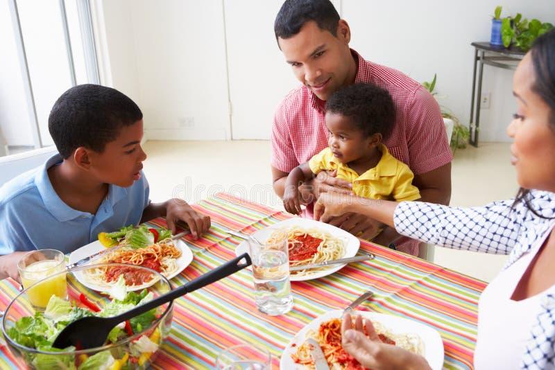 Familie die Maaltijd samen thuis eten royalty-vrije stock afbeeldingen
