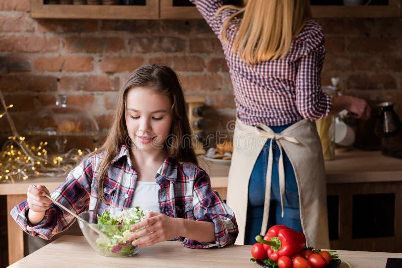 Familie, die Mahlzeithauptküchen-Salatabendessen kocht lizenzfreies stockbild