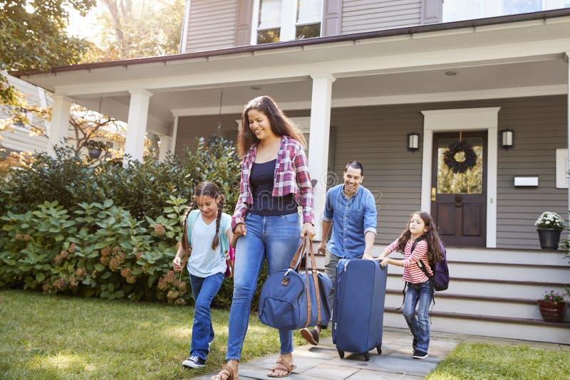 Familie die met Bagage Huis voor Vakantie verlaten stock foto