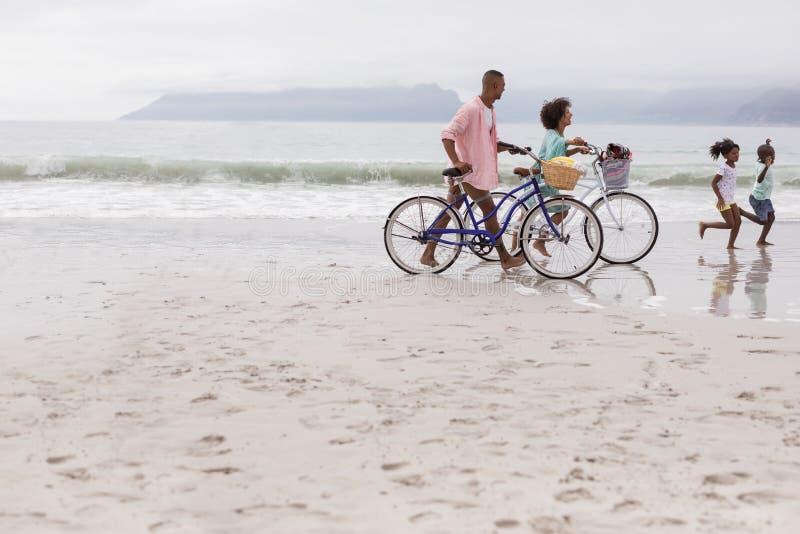Familie die met fiets op een zonnige dag lopen stock foto