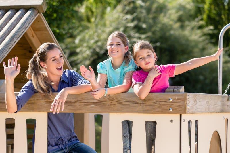 Familie die met jonge geitjes in boomhuis spelen op speelplaats stock foto's