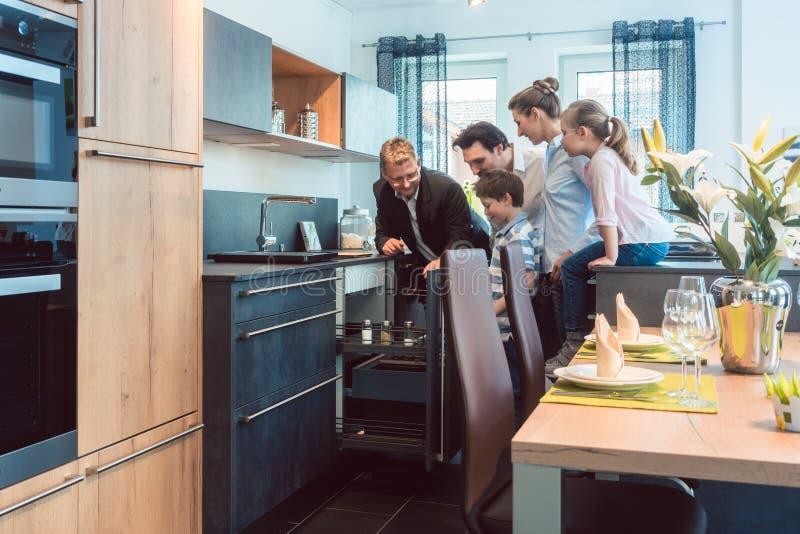 Familie die met jonge geitjes een keuken in toonzaal bekijken royalty-vrije stock afbeeldingen