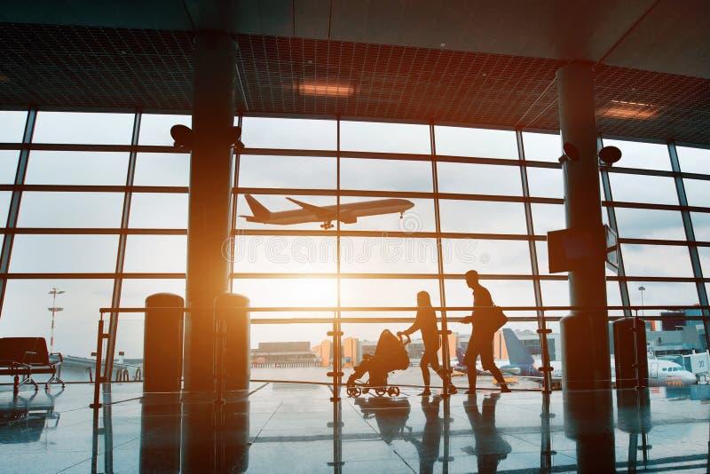 Familie die met kinderen, silhouet in luchthaven reizen stock afbeelding