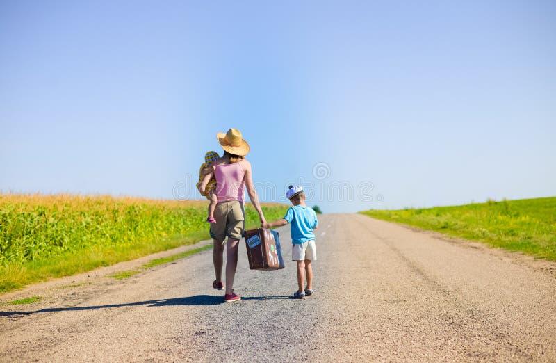 Familie die met oude koffer op de zonnige zomer lopen stock afbeelding