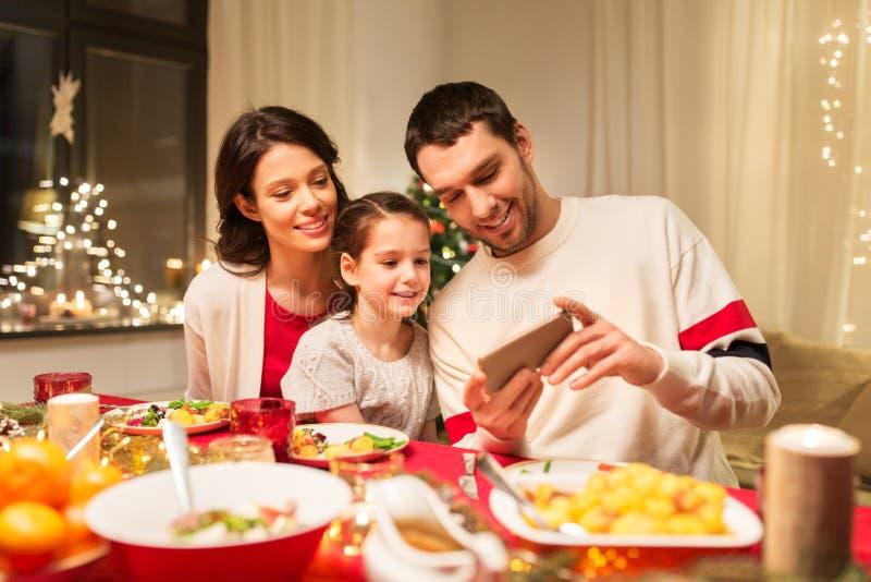 Familie die met smartphone Kerstmisdiner hebben stock afbeelding