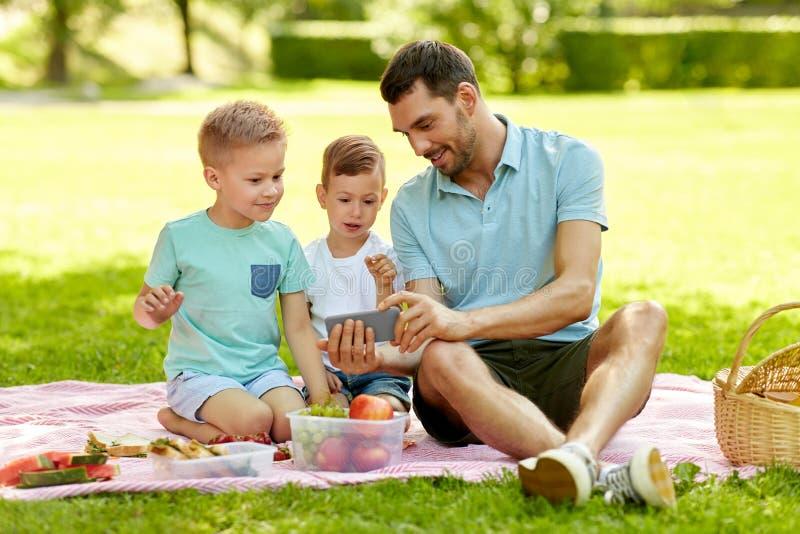 Familie die met smartphone picknick hebben bij park royalty-vrije stock foto's