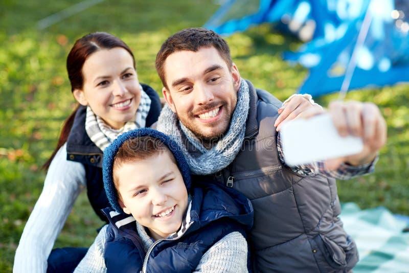 Familie die met smartphone selfie bij kampeerterrein nemen stock foto's