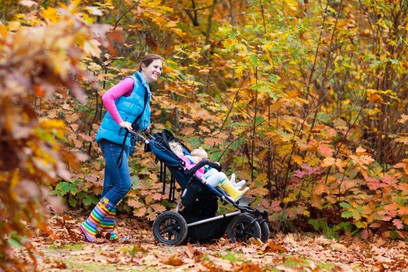 Familie die met wandelwagen in de herfstpark wandelen royalty-vrije stock afbeeldingen