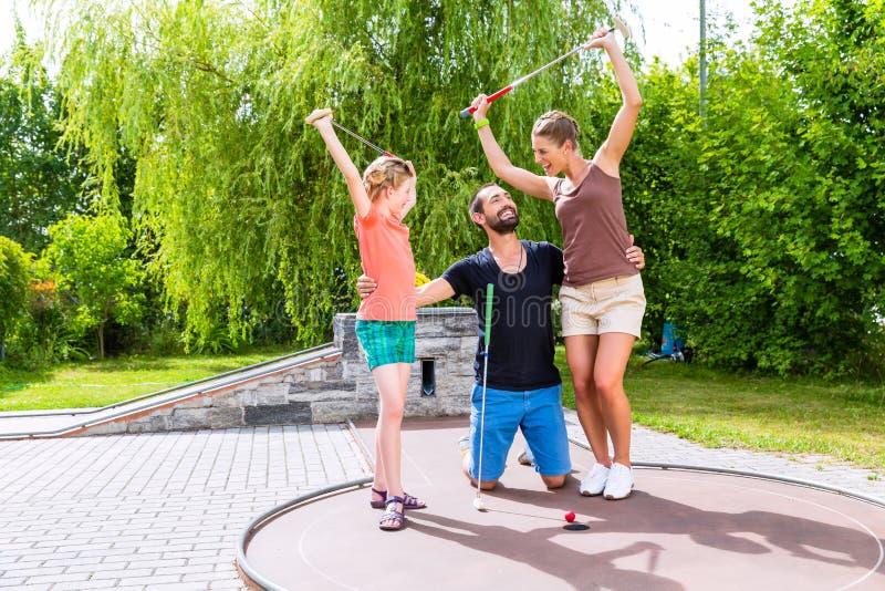 Familie, die Minigolf spielt lizenzfreies stockfoto