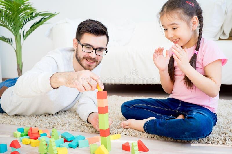 Familie, die mit Bauklötzen spielt stockbilder
