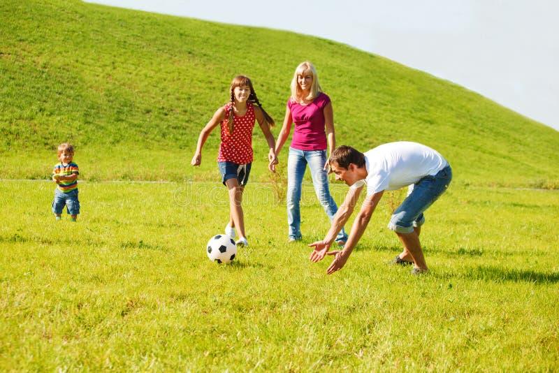 Familie, die mit der Kugel spielt lizenzfreie stockfotos