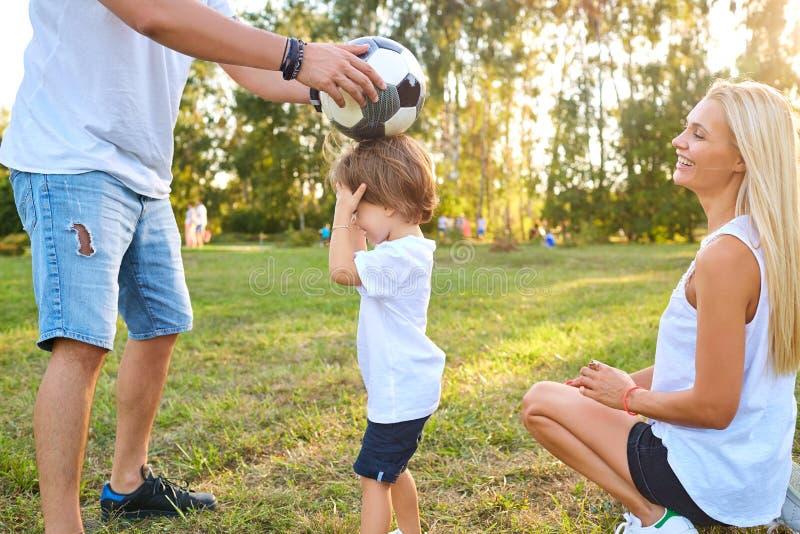 Familie, die mit einem Ball im Park spielt stockfotografie