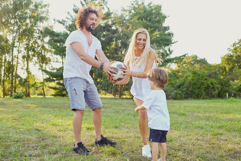 Familie, die mit einem Ball im Park spielt stockbild