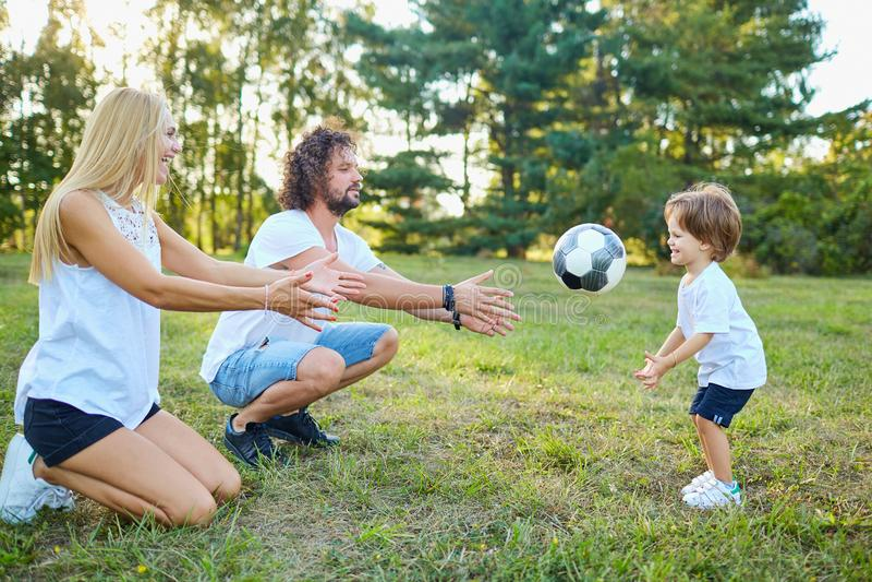 Familie, die mit einem Ball im Park spielt stockfotos