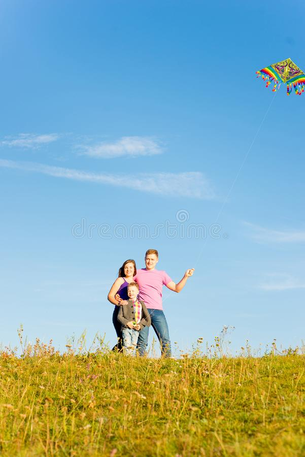 Familie, die mit einem Drachen spielt lizenzfreie stockfotografie