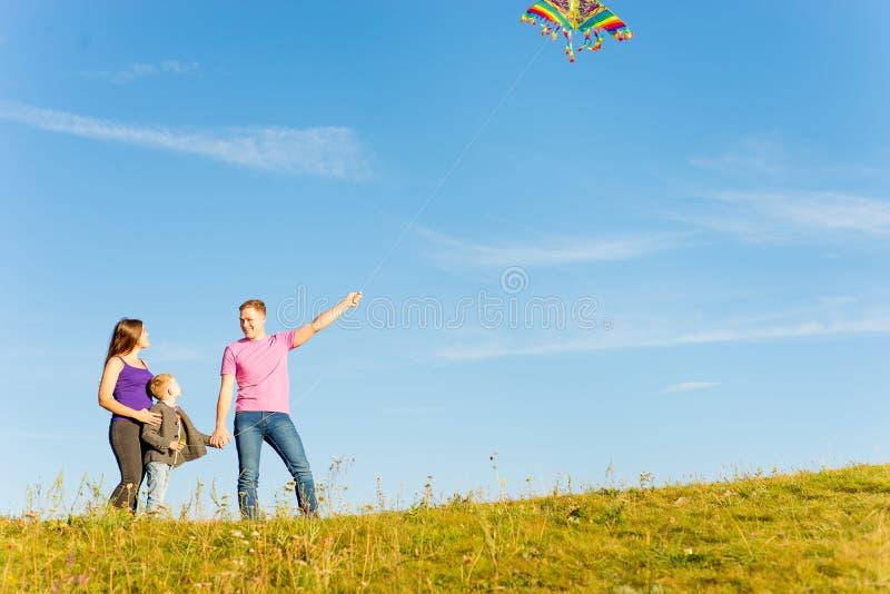 Familie, die mit einem Drachen spielt stockbild