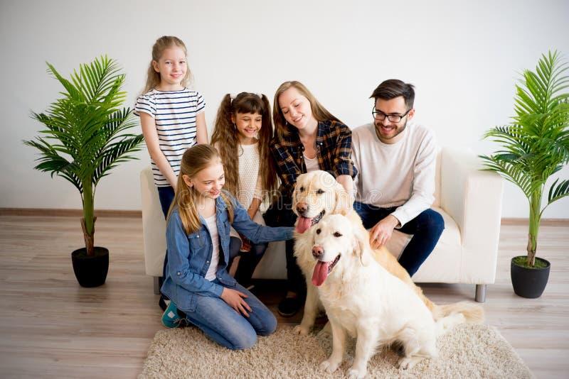Familie, die mit einem Hund spielt stockbild