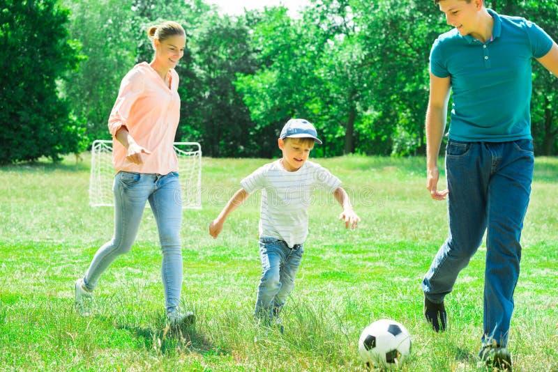 Familie, die mit Fußballkugel spielt lizenzfreie stockfotografie