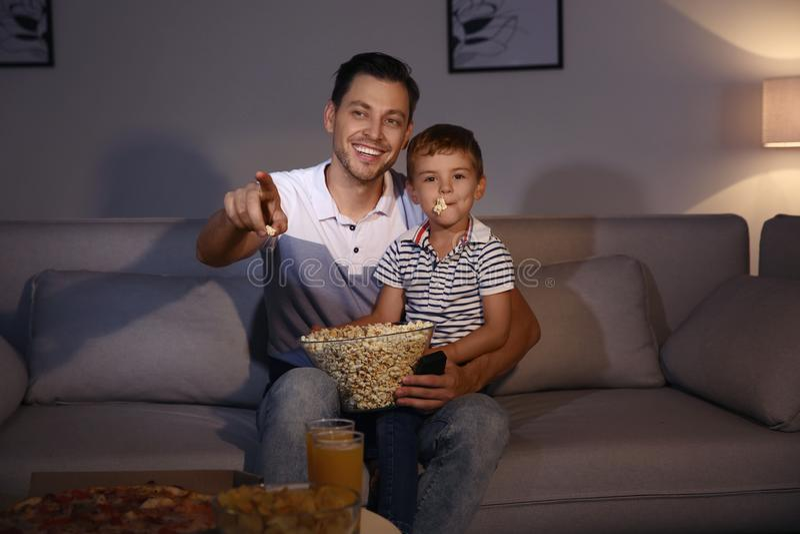Familie, die mit Popcorn im Raum zur Zeit fernsieht lizenzfreie stockfotografie