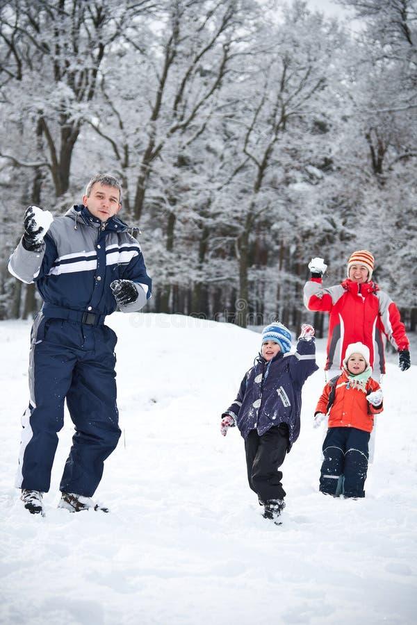Familie, die mit Schnee spielt stockbild