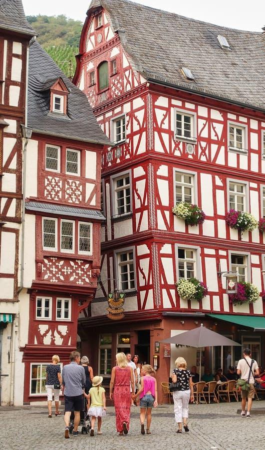 Familie, die in mittelalterliche Dorfkopfsteinstraße geht lizenzfreie stockbilder