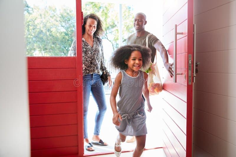 Familie, die nach Hause vom Einkaufstour unter Verwendung der freien PlastikEinkaufstüten öffnen Front Door zurückkommt stockbilder