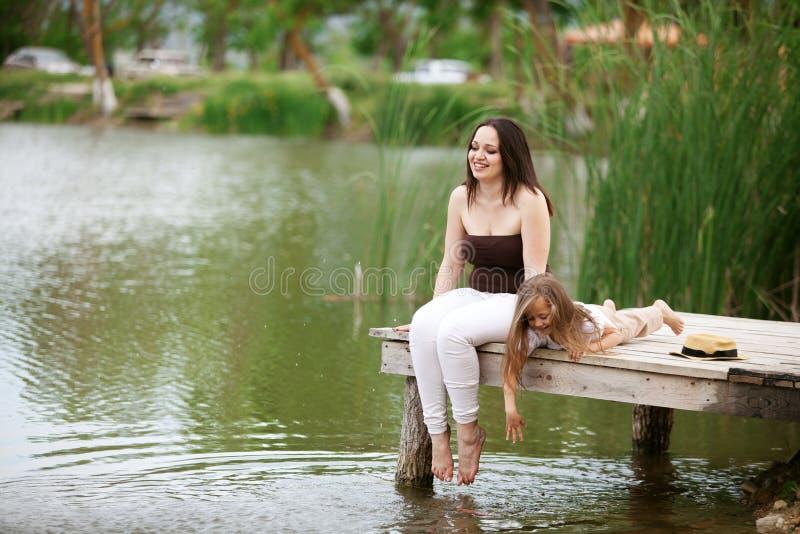 Familie, die nahe Teich stillsteht lizenzfreies stockbild