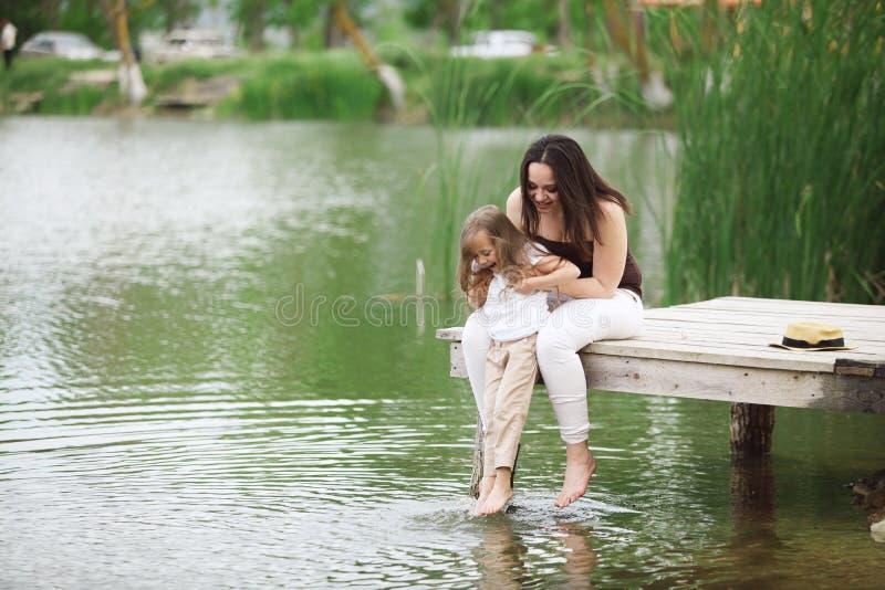 Familie, die nahe Teich stillsteht stockfotografie