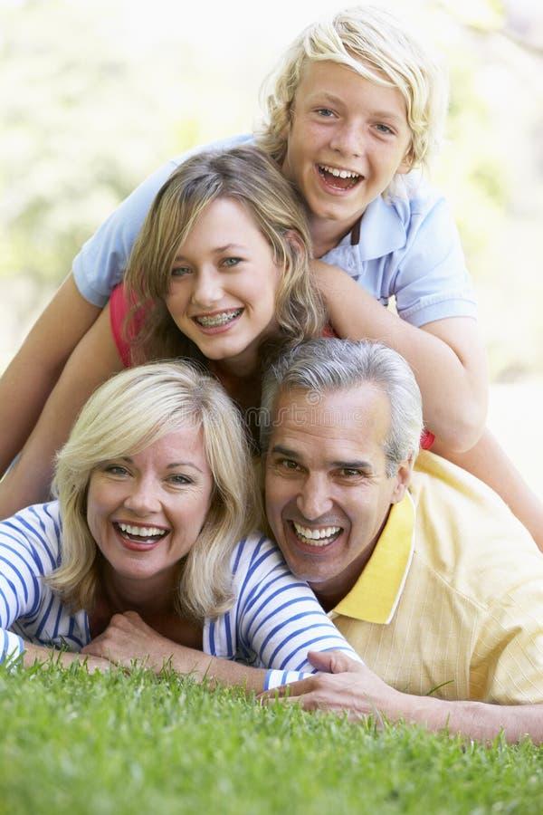 Familie, die oben auf einander in einem Park liegt stockfoto