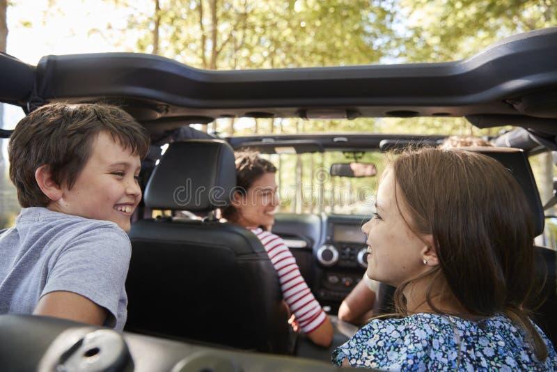 Familie, die in offenes Auto auf Landschafts-Autoreise fährt lizenzfreie stockfotos