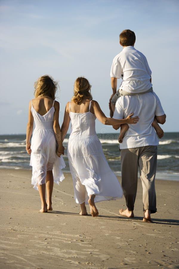 Familie die onderaan strand loopt.
