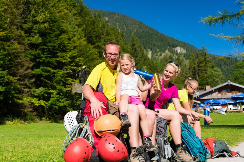 Familie die onderbreking van wandeling in de bergen hebben stock afbeelding