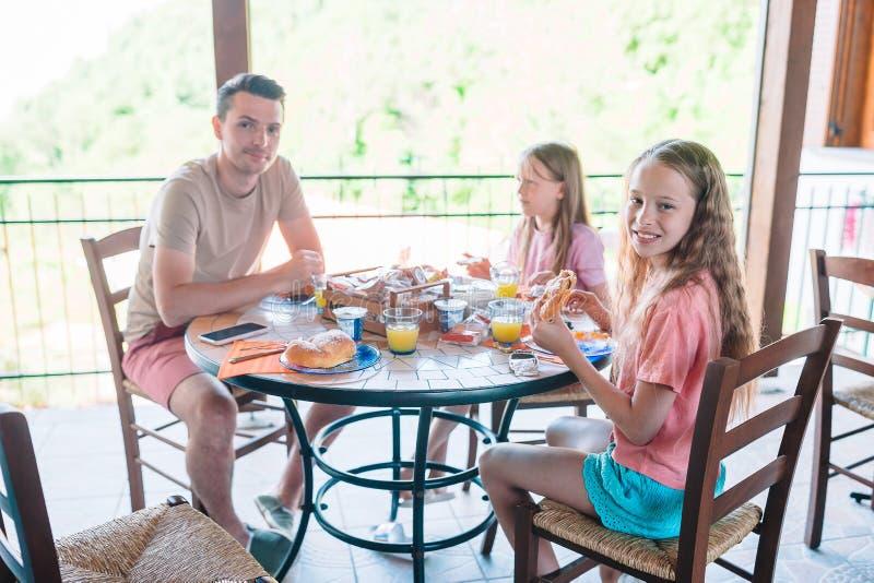 Familie die ontbijt hebben bij openluchtkoffie op terras stock afbeeldingen